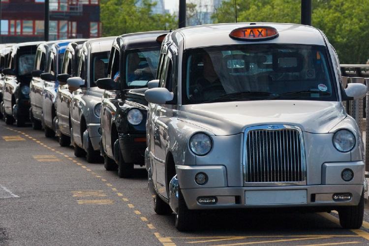 Photographie de taxis londoniens alignés le long de la route.