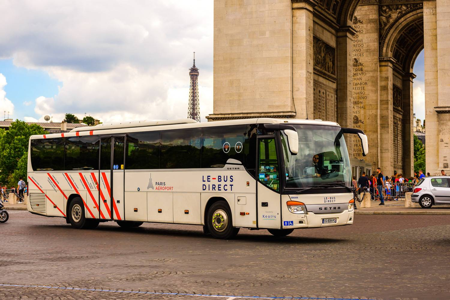 Photographie du Bus Direct sur le départ devant l'Arc de Triomphe à Paris.