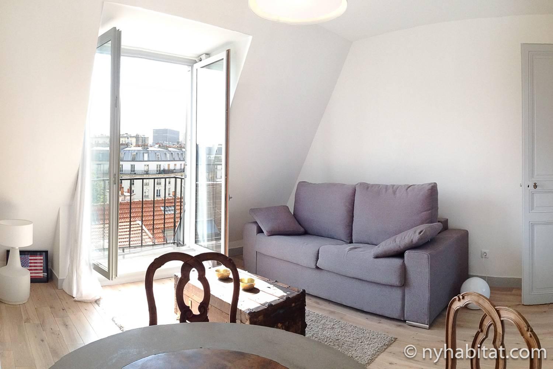 Photographie du salon de l'appartement PA-4561 dans le Quartier latin à Paris avec un canapé gris et des fenêtres.