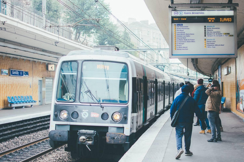 Photographie d'un RER de la ligne B arrivant à une gare dans la banlieue de Paris.