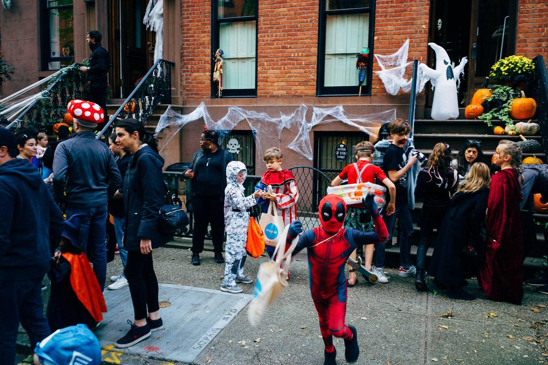 Photo d'enfants déguisés lors d'une chasse aux bonbons sur un trottoir bordant des maisons de ville new-yorkaises.