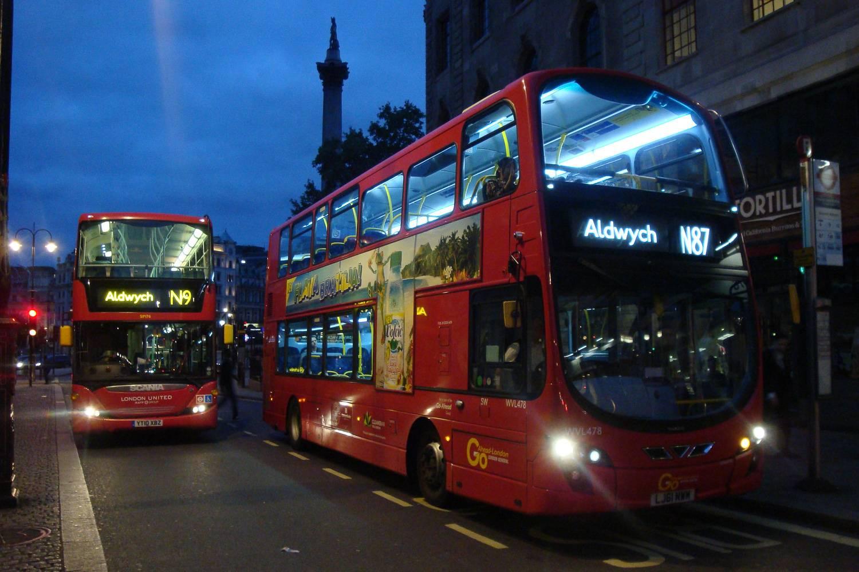 Photographie de deux bus londoniens à impériale voyageant de nuit.