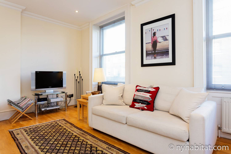 Photographie du salon de l'appartement LN-1968 dans le quartier de Marylebone, avec un canapé blanc et une télévision.