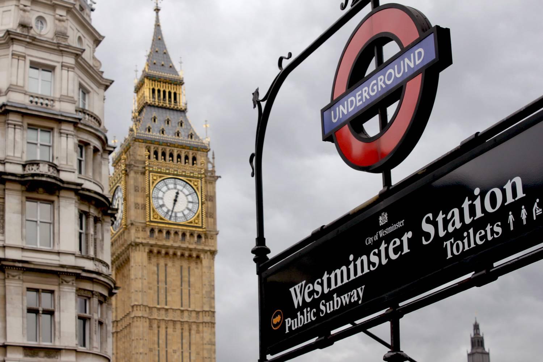 Photographie du panneau d'entrée de la station de métro Westminster devant Big Ben à Londres.