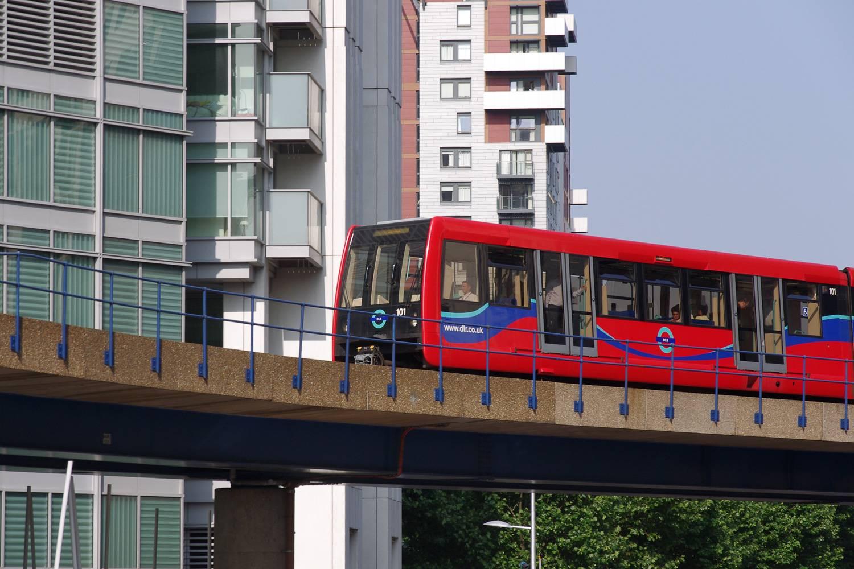 Photographie d'un train rouge de la ligne DLR se déplaçant à travers les Docks de Londres.