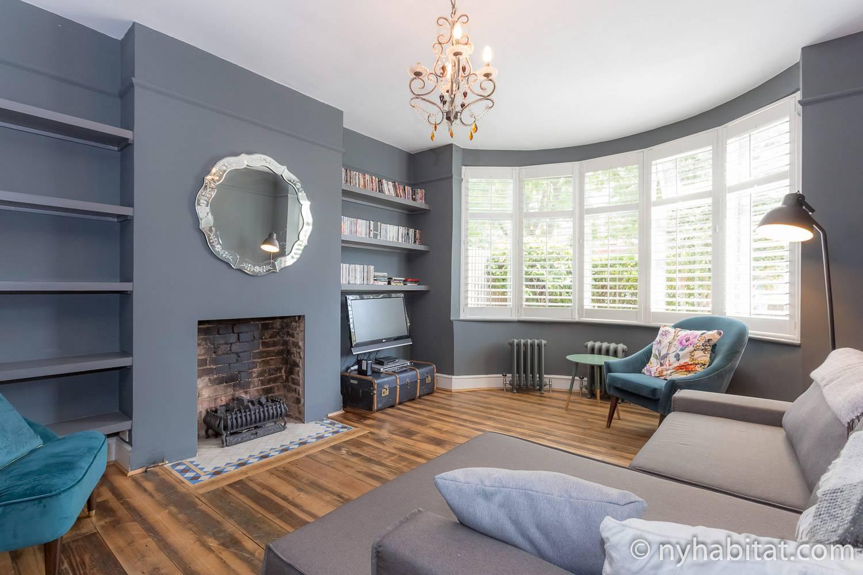 Photo d'un intérieur aux tonalités froides, d'un miroir et de meubles de salon. (Référence location : 1888)