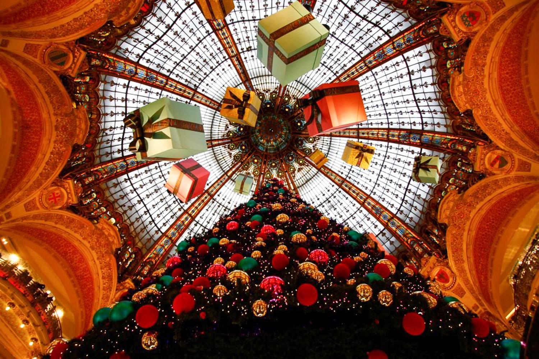 Photo de la coupole en verre du magasin principal des Galeries Lafayette, avec un imposant sapin de Noël et des cadeaux suspendus au dôme.