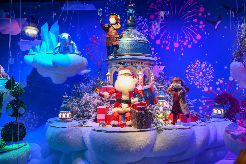 Photo d'une vitrine de Noël entourée de cadeaux, représentant des figurines animées dans un pays merveilleux hivernal, avec le père Noël au milieu.