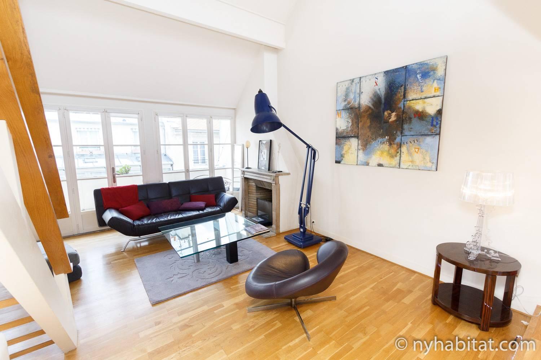 Photographie du salon de l'appartement PA-4467 avec un canapé, un fauteuil, une lampe et une cheminée décorative.