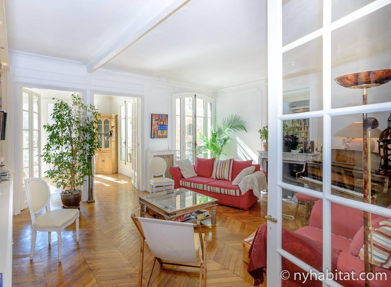 Photo de la pièce à vivre de l'appartement PA-1331 avec un canapé rouge, des fauteuils, un piano et une cheminée décorative.