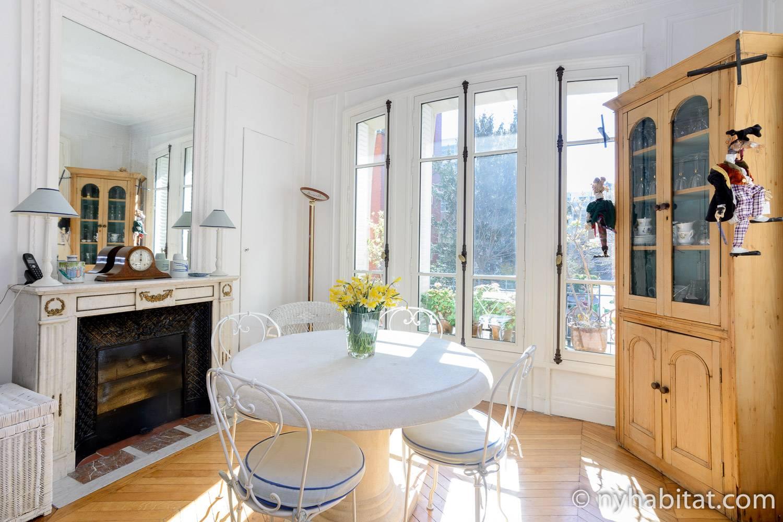 Photo de la véranda de l'appartement PA-1331 avec une petite table et des chaises, une cheminée décorative et des portes-fenêtres.