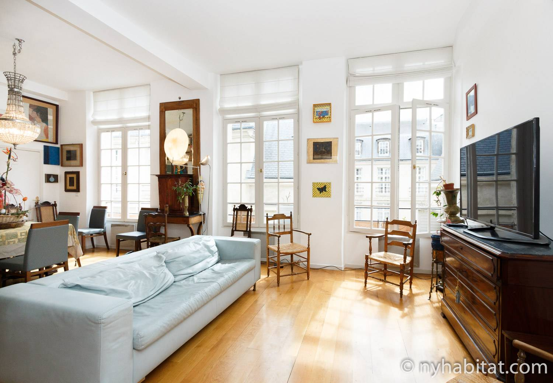 Photo de la pièce à vivre de l'appartement PA-1460 avec un canapé bleu, une télévision à écran plat et des œuvres d'art accrochées au mur.