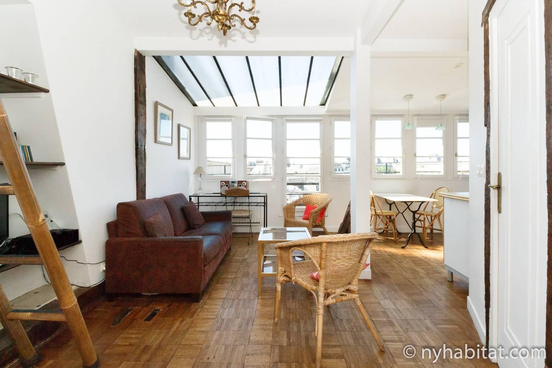 Photo de la pièce à vivre de l'appartement PA-2473 avec un canapé et des chaises.