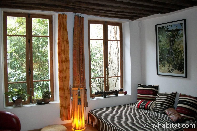 Photo du salon de l'appartement PA-4237 avec des sièges confortables, une lampe sur pied et des œuvres d'art.
