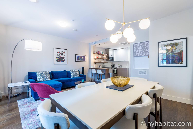Photo de l'appartement NY-17964 avec une table pour six personnes au premier plan et la cuisine entièrement équipée en arrière-plan.