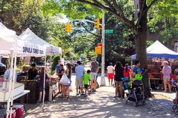 Photo du marché bio de Jackson Heights où des familles et des clients achètent des produits frais.