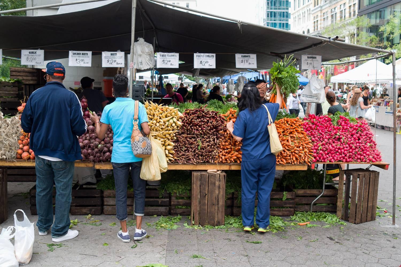Photo du marché bio d'Union Square avec des clients en train de choisir parmi toutes les variétés de fruits et légumes.