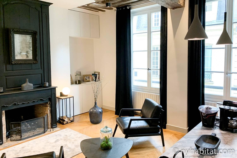 Photo du salon de la location de vacances PA-2321 dans le Marais avec des fauteuils et une cheminée.
