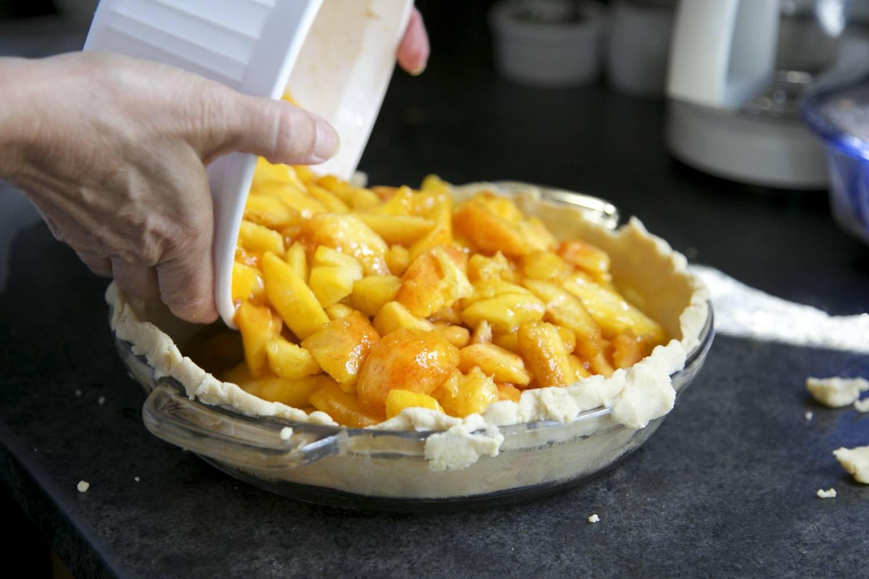 Photo de pâte à tarte dans un plat en train d'être remplie de pommes.