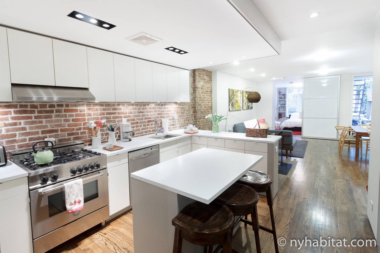 Photo de la cuisine ouverte de la location de vacances de l'Upper West Side NY-15650, avec ses placards blancs et ses murs en brique nus.