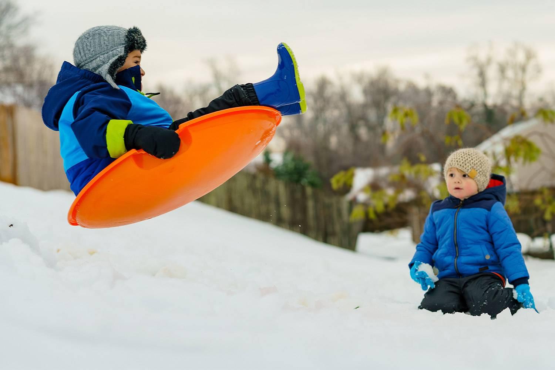 Image d'un enfant qui regarde un petit garçon voler sur une luge dans les airs et dans un paysage enneigé (Crédit photo : Unsplash)