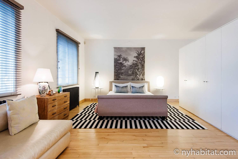 Photo de la chambre de l'appartement LN-1217 pourvue d'un lit king-size et d'une armoire.