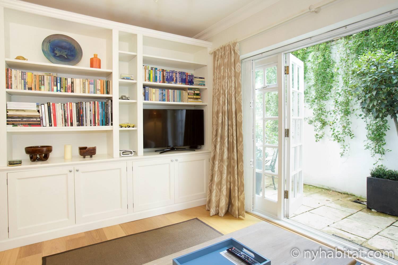 Photo de la pièce à vivre de l'appartement LN-1790, équipée d'une télévision et de portes donnant sur une terrasse.