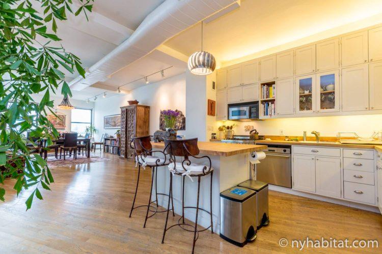 Photo de la cuisine ouverte de l'appartement NY-15771, dotée d'un îlot central avec tabourets.