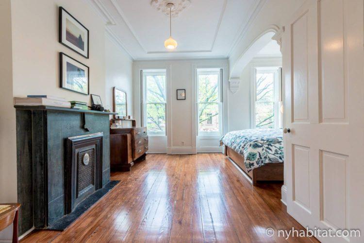 Photo de la chambre de l'appartement NY-15804 pourvue d'un lit king-size et d'une cheminée décorative.