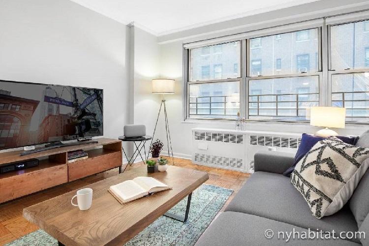Photographie du salon de l'appartement NY-11709 avec un canapé gris, une télévision, une table basse et des barreaux aux fenêtres.