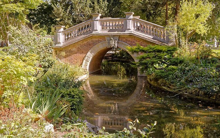 Image d'un petit pont en arc au-dessus de l'eau dans le parc (Crédit Photo : BikerNormand) [CC BY-SA (https://creativecommons.org/licenses/by-sa/2.0)]