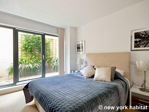 Photographie de la chambre de l'appartement LN-1240, avec lit queen size et portes coulissantes menant sur la terrasse