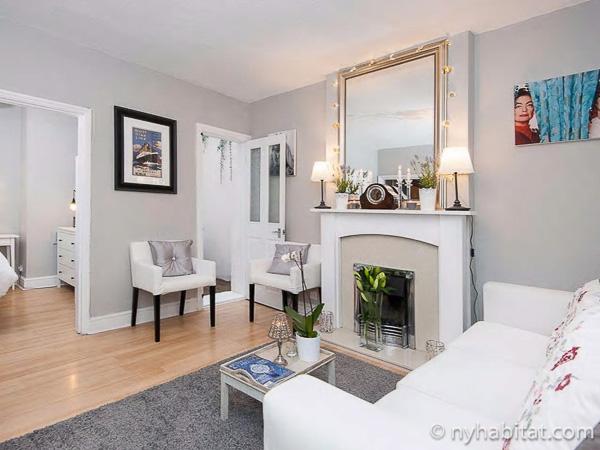 Photographie du salon de l'appartement LN-784 avec cheminée décorative, canapé et fauteuils