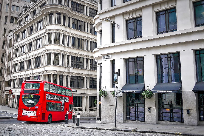 Photographie d'un bus rouge à deux étages roulant dans une rue londonienne