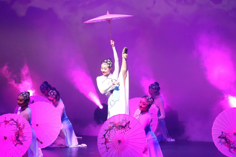 Image d'une danseuse asiatique, sous un éclairage violet, tenant sa jambe au niveau de sa tête et une ombrelle dans l'autre main