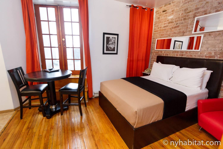 Image de la location de vacances T2 située à Lower East Side (NY-15300) avec un lit, un décor rouge et des briques apparentes