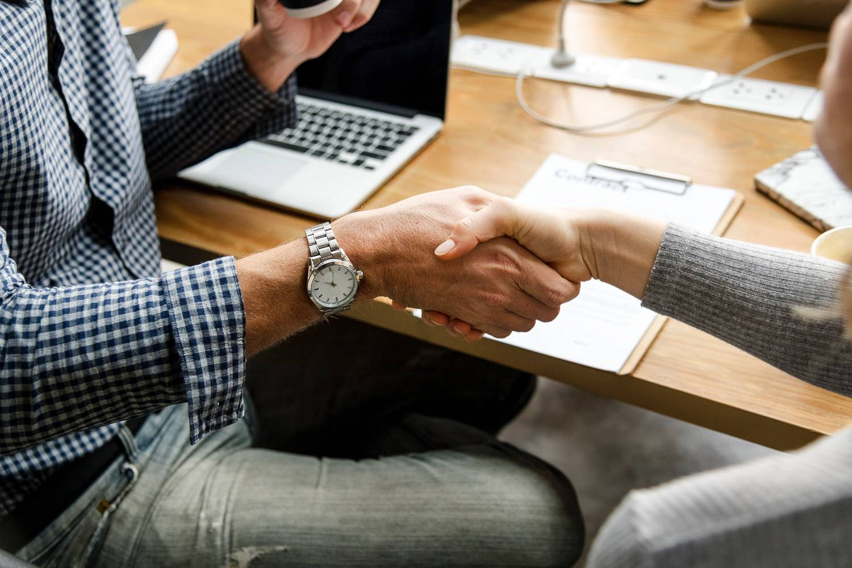 Photo de deux personnes se serrant la main par-dessus un ordinateur portable et de documents.