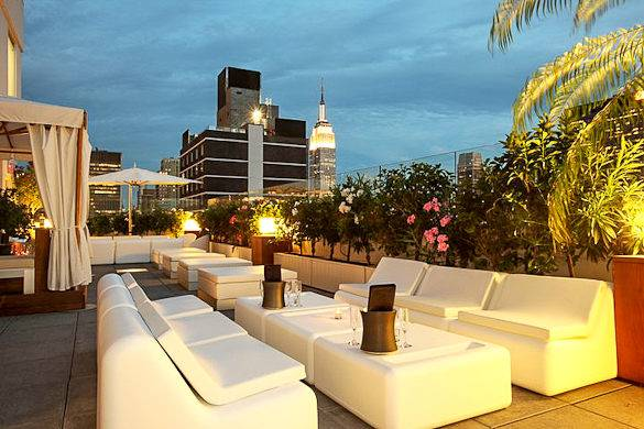 Zona lounge dello Sky Room con vista sull'Empire State Bulding a Midtown, Manhattan
