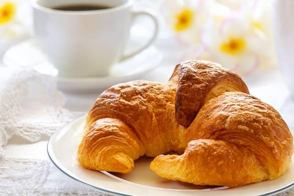 Immagine di un cornetto francese con del caffè