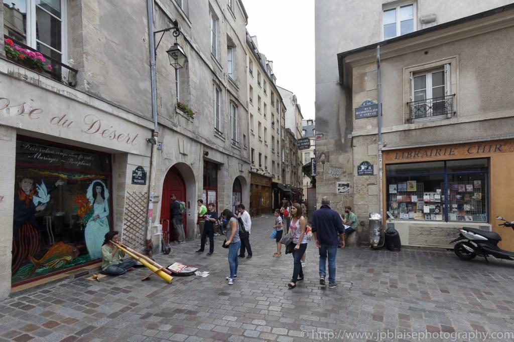 Immagine di un musicista che intrattiene I turisti su una strada di pietra a Le Marais, Parigi