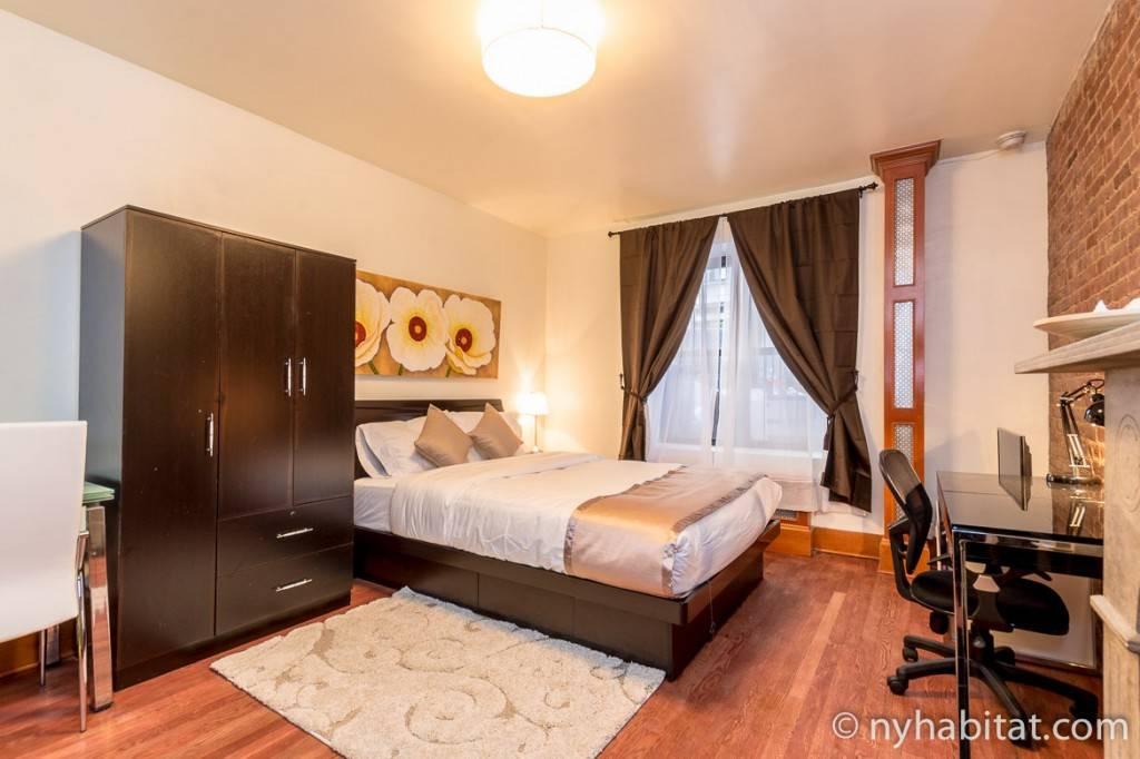 Camera da letto con parete in mattoncini, ampia finestra e una scrivania.