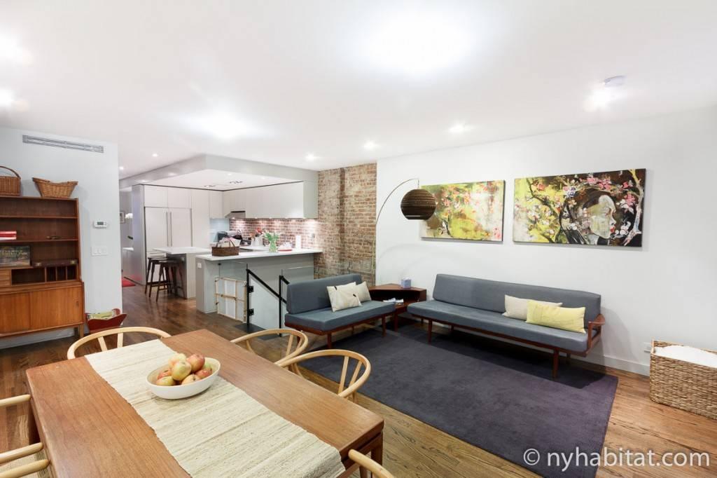 Appartamento con soggiorno aperto, cucina, tavolo da pranzo e colori a contrasto.