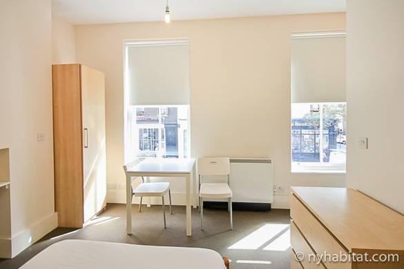 Fotodella stanza di LN-1509 arredata con scrivania, armadio e letto.