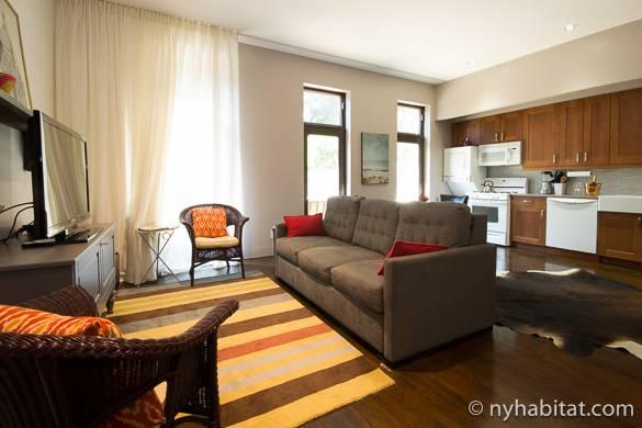 Foto del divano e della TV nel salotto dell'appartamento NY-15441, da cui si intravede la cucina come sfondo