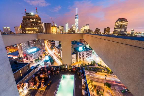 Foto della piscina sul tetto al James Hotel circondata dallo skyline di New York