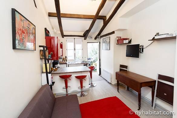 Foto del salotto del PA-16115 con particolari in rosso e le travi a vista sul soffitto