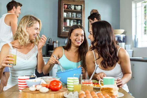 Immagine di 5 persone che socializzano in una cucina davanti al cibo.