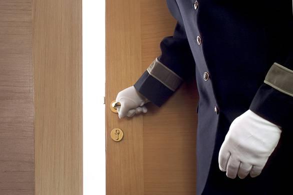 Alt 4: Immagine di un portiere che sta aprendo una porta.