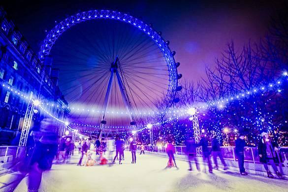 Immagine di persone mentre pattinano sul ghiaccio di sera con il London Eye illuminato come sfondo.