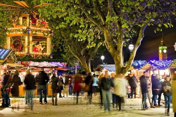 Immagine dei mercatini di Natale al Tate di sera con luci natalizie e persone